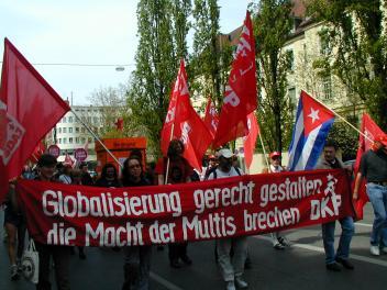 Demo mit Fahnen und Transparent: »Globalisierung gerecht gestalten, die Macht der Multis brechen. DKP«.